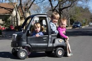 3 enfants jouant dans une voiture jouet