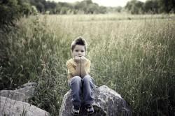 petit garçon assis sur un rocher
